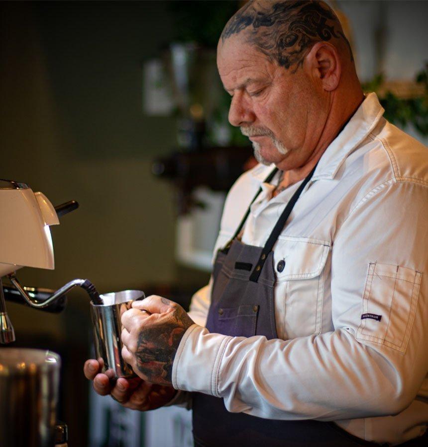 Mann med tattoveringer steamer kaffe